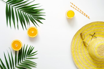 Summer or travel concept.Palm branches, hat, sunglasses and orange juice on white background. Flat lay, top view.Copy space