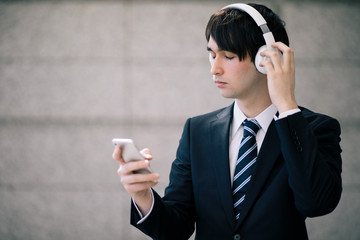 young man wearing wireless headphone and listening to music with smart phone