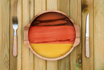 Concept of German cuisine. Wooden plate with a German flag, fork and knife on a wooden background
