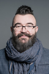 Smiling bearded man in a scarf and glasses with mohawk hairstyle on a gray background
