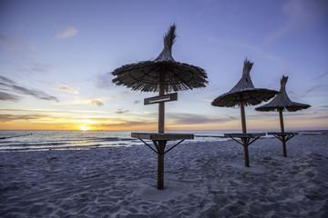 Drei Sonnenschirme einer Strandbar an der Ostsee im Sonnenuntergang