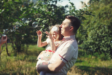 Little girl with her father playing in the Park, blowing bubbles. Happy family laughing.