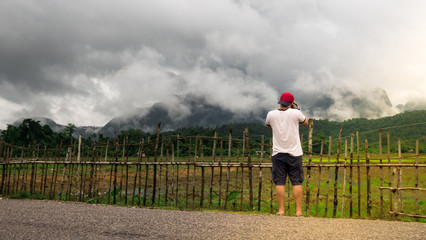 Asian male tourist photographer in VangVieng