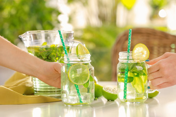 Women taking mason jars of refreshing lemonade on table