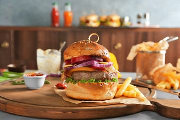 Fresh homemade burger with ketchup and vegetables on wooden board
