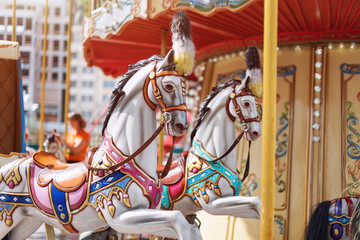 Horses on a carnival Merry Go Round. Old French carousel in a holiday park. Big roundabout at fair in amusement park.