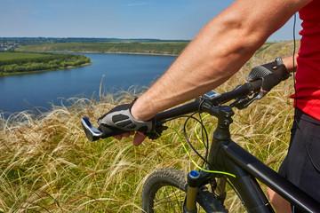 Cyclist travel on mountain bike through green meadow against beautiful sky.