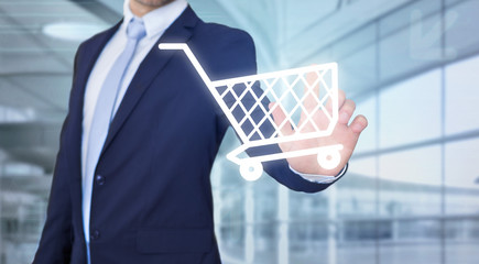 Businessman touching technology interface with trolley - Online shopping concept
