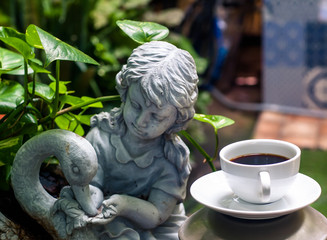 coffee cup and Sculpture of angel, Morning light