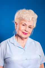 Elderly woman smiling on a blue background, space for text