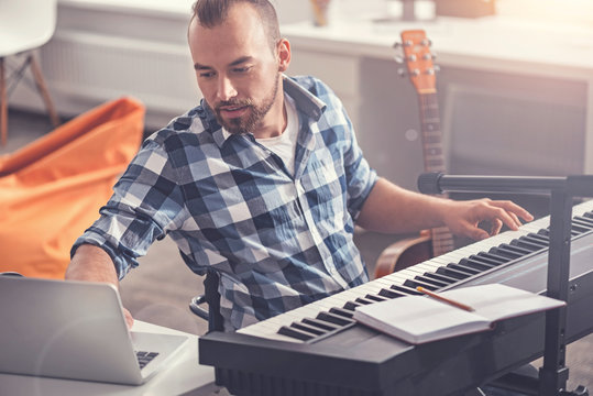 Confident accomplished musician using his laptop