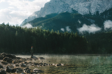 Woman gazing over a mountain lake with forest in Germany in the morning