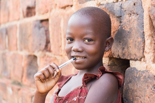 An 11-year old black Ugandan girl smiling and holding a pen against her mouth and leaning against a brick wall looking at the camera
