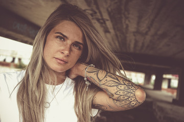 Portrait of a young beautiful blonde in a white T-shirt and with tattoos, looks at the camera, close-up