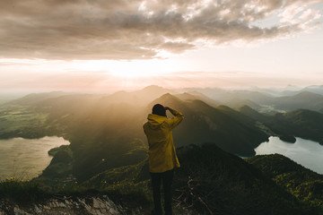 Male photographer in yellow jacket looking over a valley with mountains, forest and lake in Germany in the morning