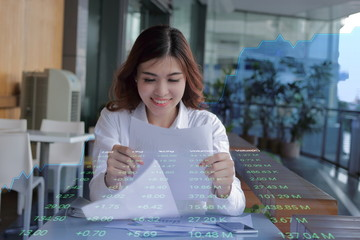 Double exposure of young attractive businesswoman looking document on paperwork against showing growth graphic on background. Business success concept.