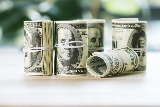 close up view of dollar banknotes in rolls with rubber bands on table