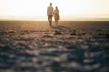 Obraz Couple in love walking on the beach and looking at each other - fototapety do salonu