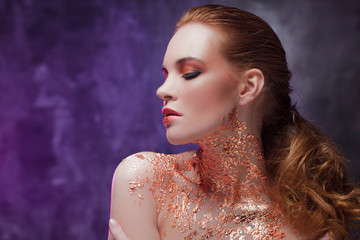 Beautiful girl with creative image with gold foil on the neck. Blue and purple toning