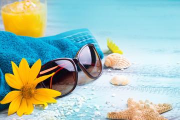Urlaubszeit - Deko mit Sonnenbrille, Handtuch, Muscheln, Cocktail und Blumen