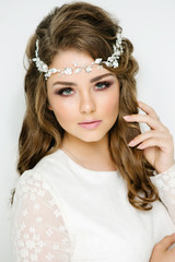 Beautiful model with an elegant hairstyle. Girl with fashion hairstyle for wedding and gentle makeup on white background