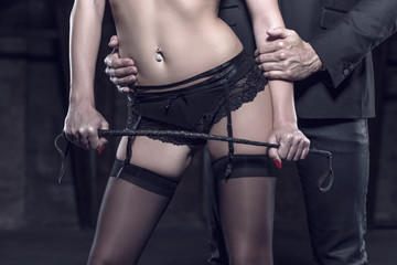 Sexy dominant woman with whip seducing rich man closeup