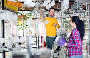 Young man and woman are choosing stylish and modern suspended lamp.
