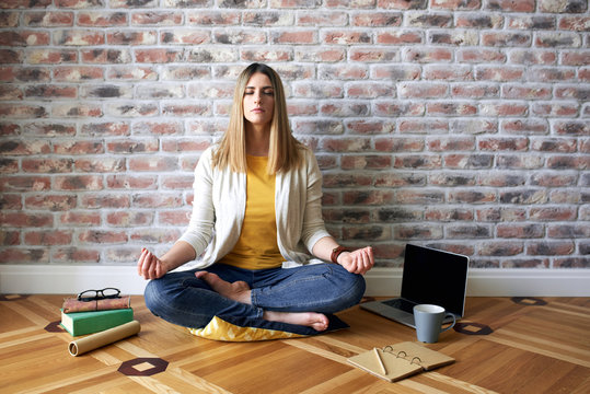 Young woman sits on the floor and meditates
