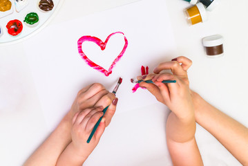 Child's hands painting a heart