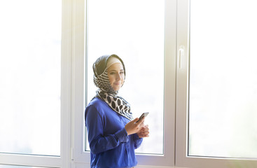 portrait of happy asian woman wearing hijab calling with mobile phone