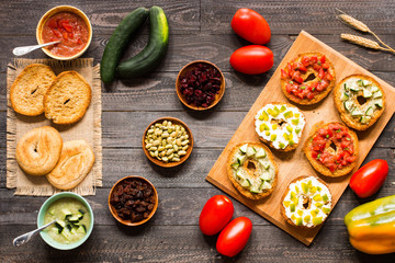Italian bruschetta with cheese, tomato sauce, cucumber sauce, and herbs, on a wooden background.