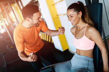 Young attractive woman doing exercises in gym with personal trainer