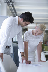 Businessman And Businesswoman Discuss Document In Office