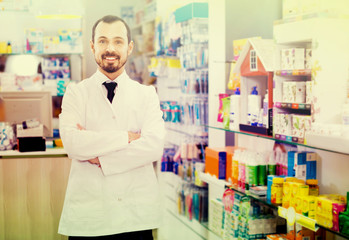 Male pharmacist demonstrating assortment of drugs