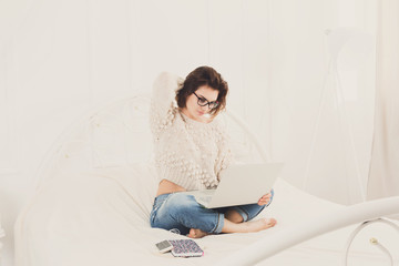 Young woman freelancer with laptop in bed