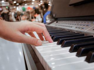 close up of hand playing piano keys
