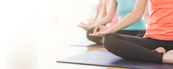 In de dag School de yoga Attractive young Asian woman group exercising and sitting in yoga lotus position in yoga classes Breath control with copy space