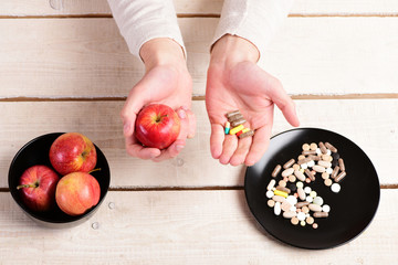 Male hands hold apple and pills at wooden table