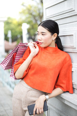 Asian woman holding shopping bag with attractive sililng at outdoor place. Woman with shopping concept.