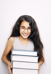 Adorable girl studying with eyeglasses and books in the hand on white background