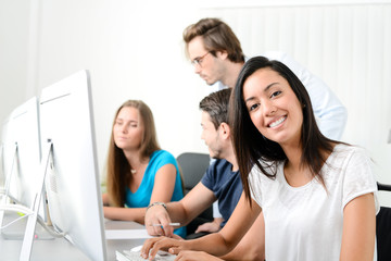 portrait of young ethnic woman with people in business school office classroom working on desktop computer with teacher
