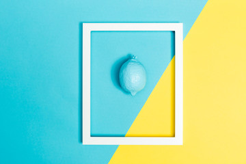 Painted blue lemon with frame on a bright split tone background