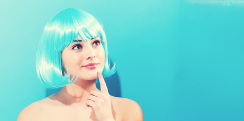 Wall Mural - Beautiful woman in a bright blue wig on a blue background