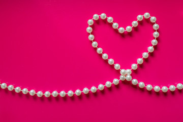 White pearl heart on a bright pink background. Pearl beads in the shape of heart. Glamorous background for processing