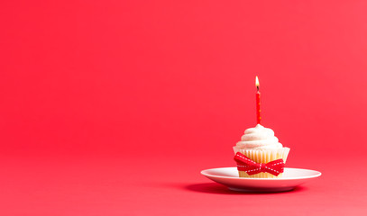 Cupcake with candle celebration theme on a red background