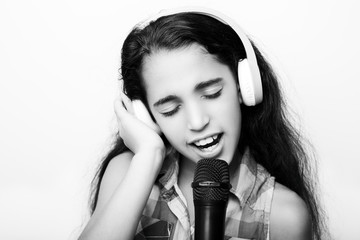 Afro-American little girl with headphones and microphone on white background