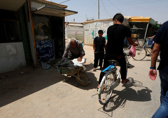 A Syrian man arranges his belongings on a wheelbarrow at the main market in Al Zaatari refugee camp outside the city of Mafraq in Jordan, near the border with Syria