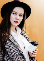 young pretty hipster girl student with coffee cup posing adorable smiling, lifestyle people concept outdoor