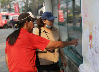 Wildfire evacuees Bary Squinas and Celia Stobie from Williams Lake look over a map of the evacuation zone outside of the evacuation centre in Kamloops
