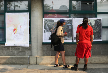 Wildfire evacuees Celia Stobie and Bary Squinas from Williams Lake look over a map of the evacuation zone outside of the evacuation centre in Kamloops